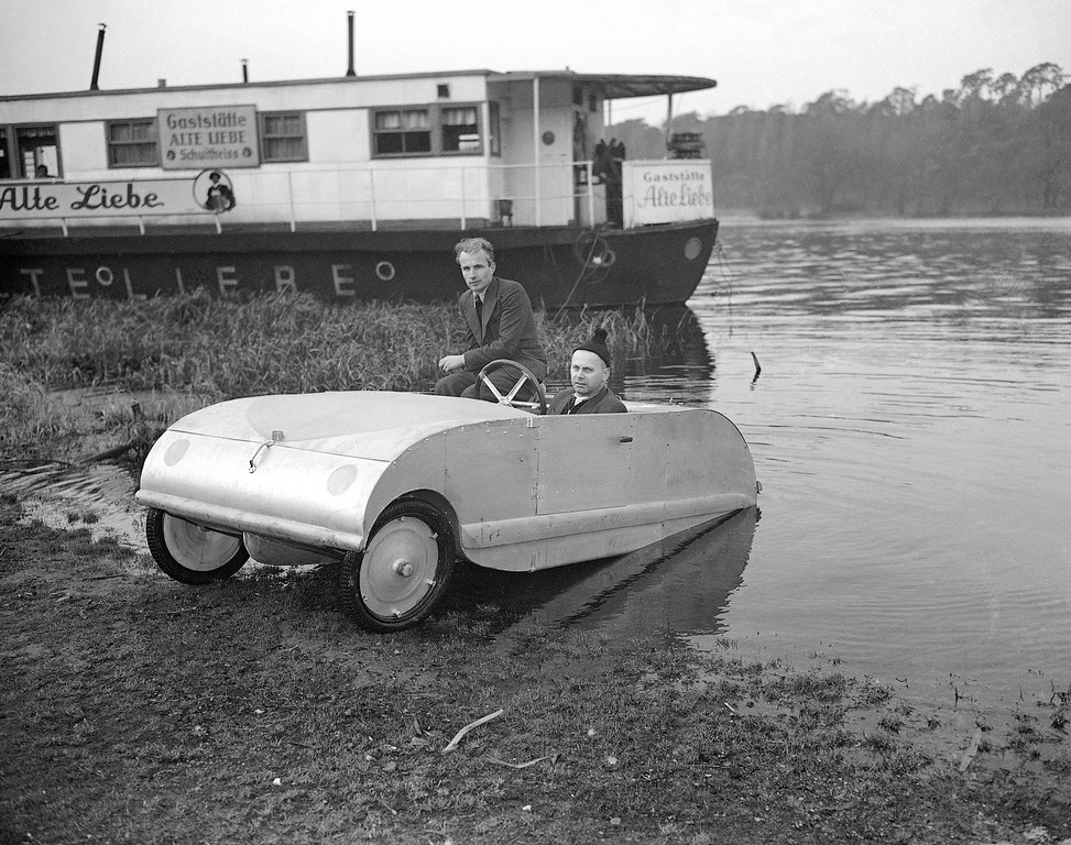 . Karl Baier, at wheel, and a passenger, test out the new midget amphibious car that was developed by Baier in West Berlin, Germany. Jan. 22, 1952. Baier has simplified construction of the vehicle so that the motor, steering system, gear case, clutch, all cables and even the brakes are inside the body. (AP Photo/Heinrich Sanden Jr.)