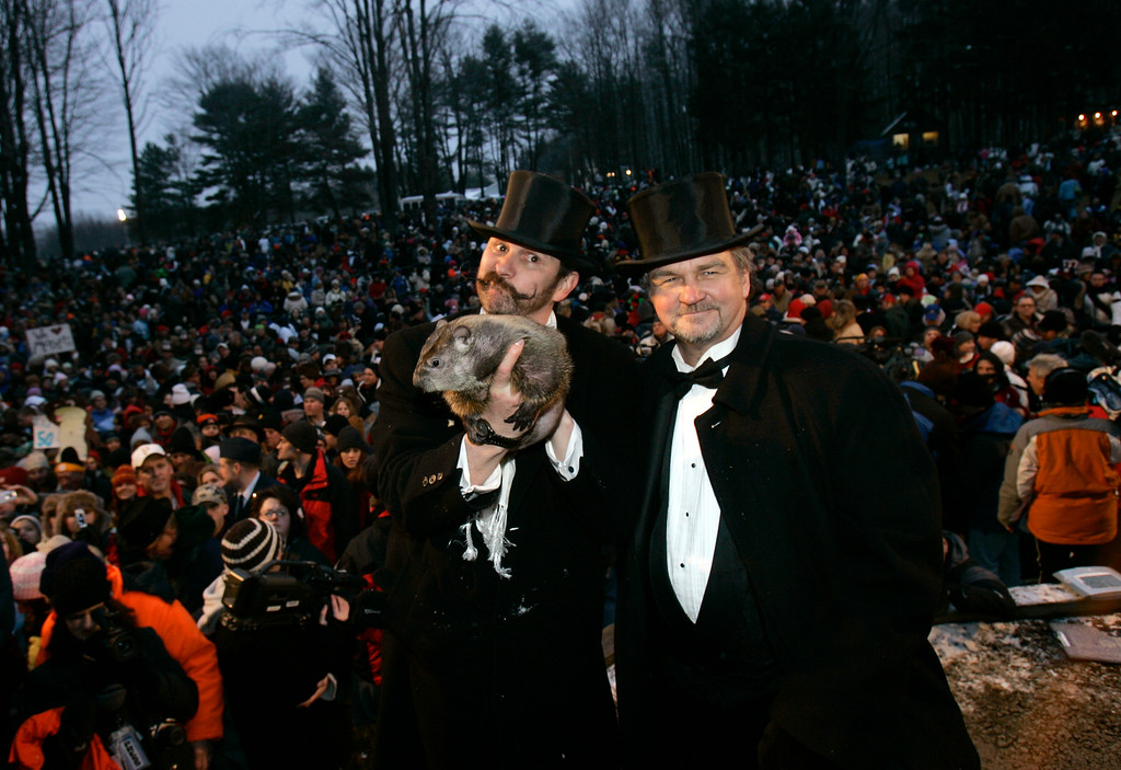 . Punxsutawney Phil, the weather predicting groundhog, is held up by his handlers Ben Hughes, left, and John Griffith to one of the largest crowds ever who came to hear the prediction of an early spring in Punxsutawney, Pa., Friday, Feb. 2, 2007.   Phil did not see his shadow on Friday which, according to German folklore, means folks can expect an early spring instead of six more weeks of winter.     (AP Photo/Carolyn Kaster)