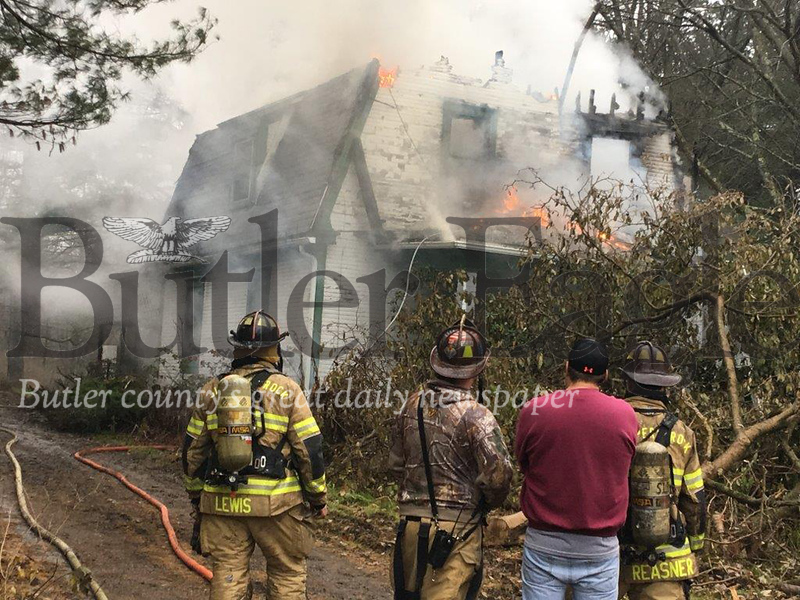 A vacant house on Stamm Road in Slippery Rock Township burns Tuesday morning as Slippery Rock volunteer firefighters and owner James Patridge look on.