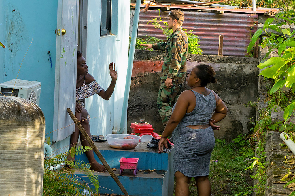 . Two local women chat as a Dutch Marine helps out in preparation for the arrival Hurricane Maria, in Oranjestad, Statia, on the Leeward Islands, Monday, Sept. 18 2017. Maria has intensified into a Category 5 hurricane as its eye is approaching Dominica in the eastern Caribbean, the U.S. Hurricane Center said in a statement on Monday evening. (AP Photo/Stephan Kogelman)