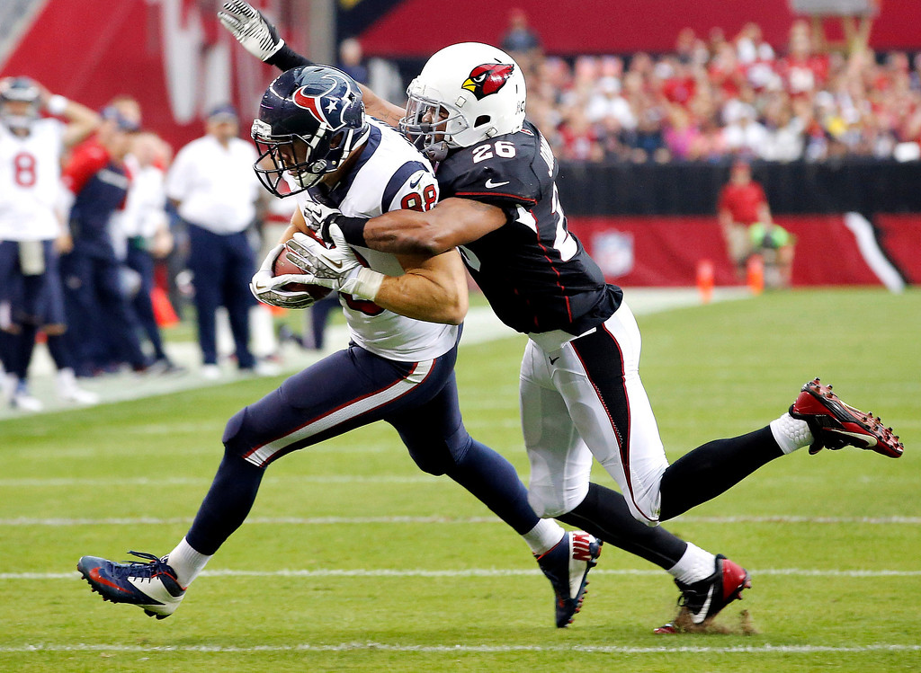 . Houston Texans tight end Garrett Graham, left, is tackled by Arizona Cardinals free safety Rashad Johnson (26) during the first half of an NFL football game Sunday, Nov. 10, 2013, in Glendale, Ariz. (AP Photo/Ross D. Franklin)