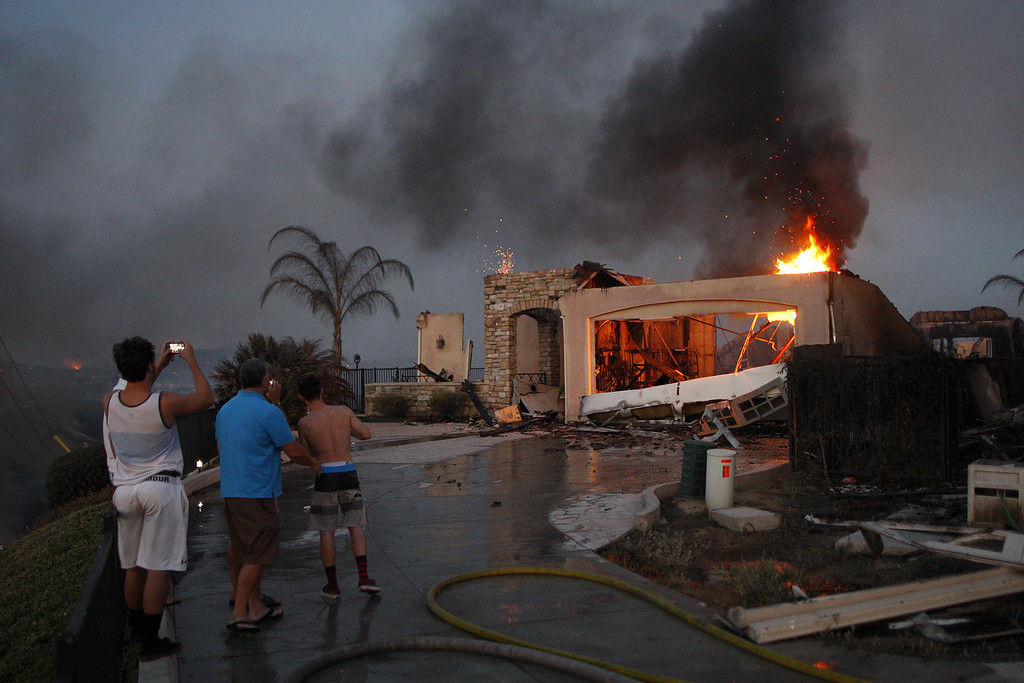 . Residents photograph the burning ruins of their home that was destroyed in the Poinsettia fire, one of nine wildfires fueled by wind and record temperatures that erupted in San Diego County throughout the day, on May 14, 2014 in Carlsbad, California. Fire agencies throughout the state are scrambling to prepare for what is expected to be a dangerous year of wildfires in this third year of extreme drought in California. The Poinsettia fire has destroyed at least eight homes and severely damaged eight condos and two businesses.  (Photo by David McNew/Getty Images)