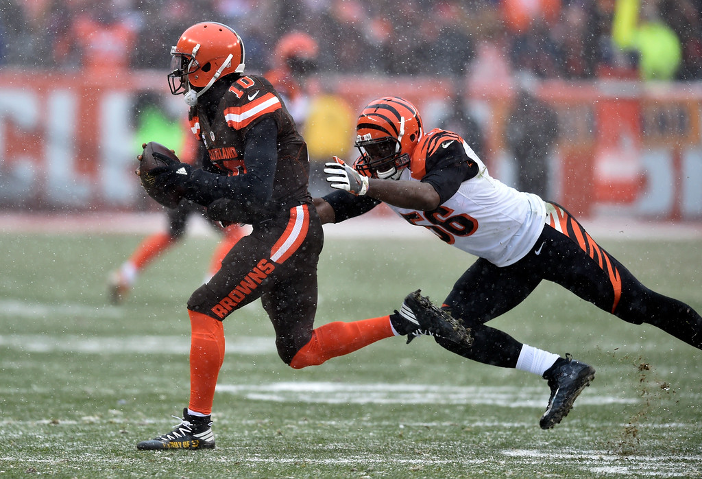. As snow falls, Cleveland Browns quarterback Robert Griffin III (10) scrambles away from Cincinnati Bengals outside linebacker Karlos Dansby (56) in the first half of an NFL football game, Sunday, Dec. 11, 2016, in Cleveland. (AP Photo/David Richard)