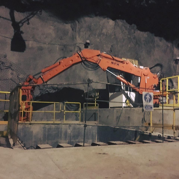 NPK B550 pedestal boom system with GH7 hydraulic hammer-breaking bridged rock abover a grizzly style crusher in a mine (4).jpg