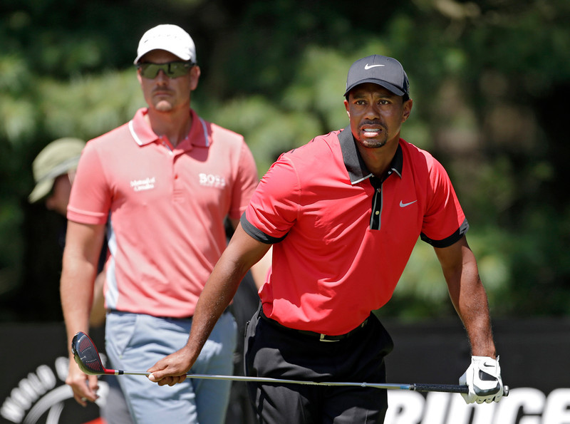 . Tiger Woods watches his tee shot on the second hole with Henrik Stenson, from Sweden, left, during the final round of the Bridgestone Invitational golf tournament Sunday, Aug. 4, 2013 at Firestone Country Club in Akron, Ohio. (AP Photo/Mark Duncan)