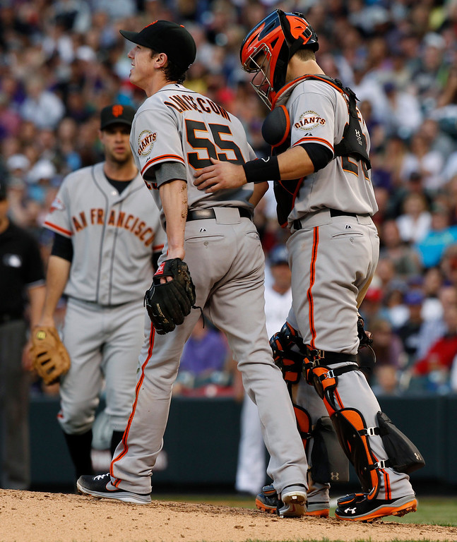 . San Francisco Giants starting pitcher Tim Lincecum (55), left, is checked by catcher Buster Posey after losing his footing while delivering a pitch against the Colorado Rockies in the fourth inning of a baseball game in Denver, Saturday, May 18, 2013. Lincecum was called for a balk on the misstep. (AP Photo/David Zalubowski)