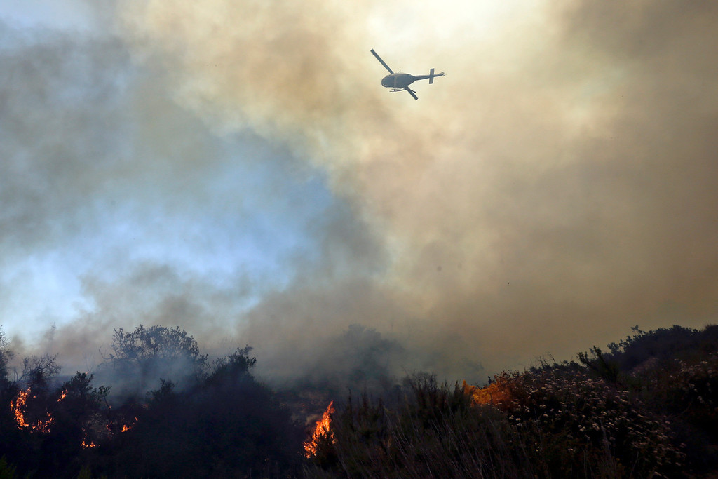 . A helicopter flies over burning vegetation as it nears homes Wednesday, May 14, 2014, in Carlsbad, Calif. More wildfires broke out Wednesday in San Diego County  threatening homes in Carlsbad and forcing the evacuations of military housing and an elementary school at Camp Pendleton as Southern California is in the grip of a heat wave. (AP Photo)