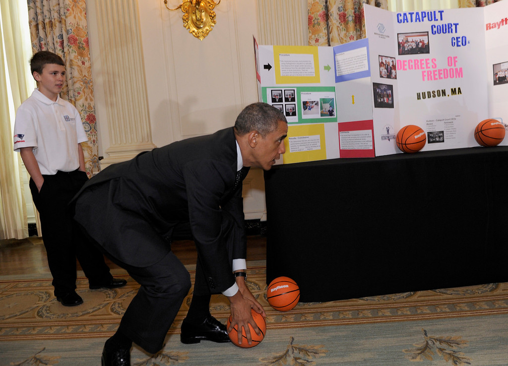 . President Barack Obama tries to catch a basketball as Gerry McManus, 13, of Hudson, Mass., watches, during a tour of the 2014 White House Science Fair exhibits that are on display in the State Dining Room at the White House in Washington, Tuesday, May 27, 2014. McManus and two other students showed Obama their basketball catapult. (AP Photo/Susan Walsh)