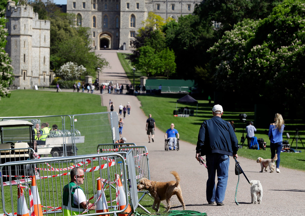 . Dog walkers along the Long Walk as technicians prepare facilities for the wedding in Windsor, England, Monday, May 14, 2018. Preparations are being made in the town ahead of the wedding of Britain\'s Prince Harry and Meghan Markle that will take place in Windsor on Saturday May 19. (AP Photo/Kirsty Wigglesworth)