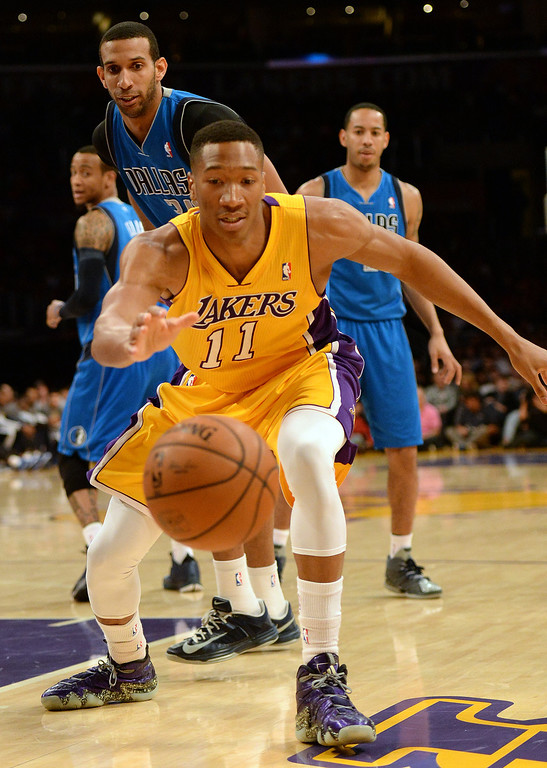 . Los Angeles Lakers forward Wesley Johnson (11) reaches for a loose ball against the Dallas Mavericks in the first quarter during an NBA basketball game in Los Angeles, Calif., on Friday, April 4, 2014.  (Keith Birmingham Pasadena Star-News)