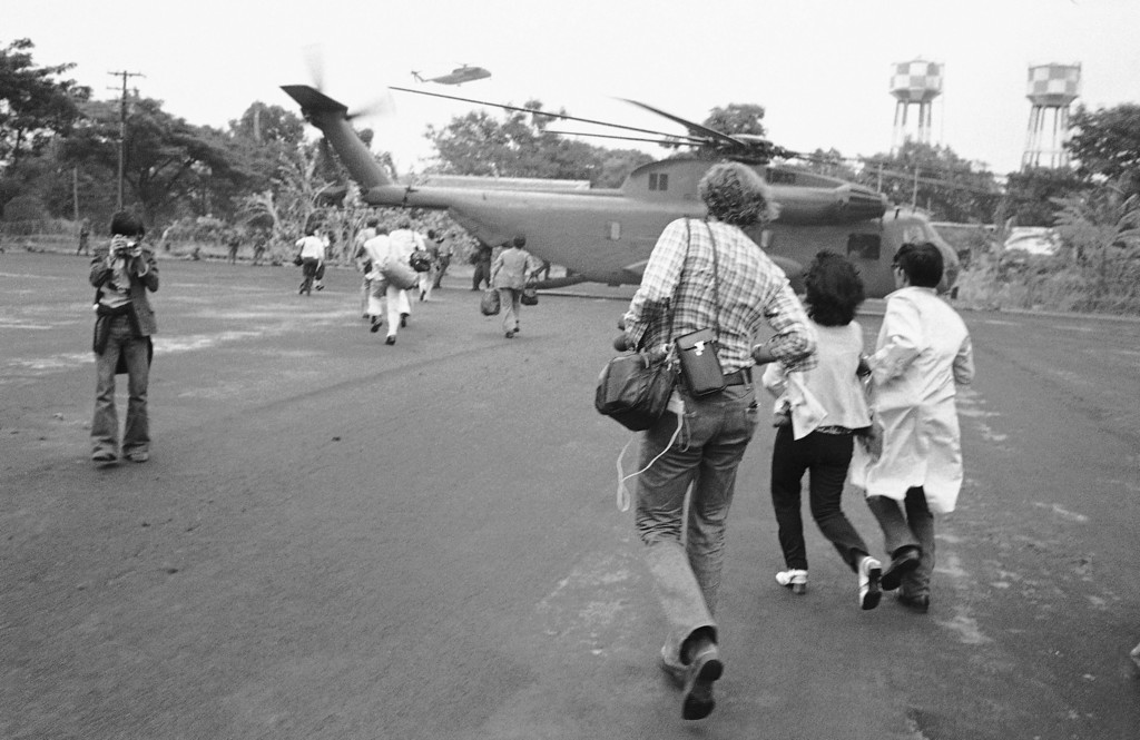 . Americans and Vietnamese run for a U.S. Marine helicopter in Saigon during the evacuation of the city, April 29, 1975. (AP Photo)