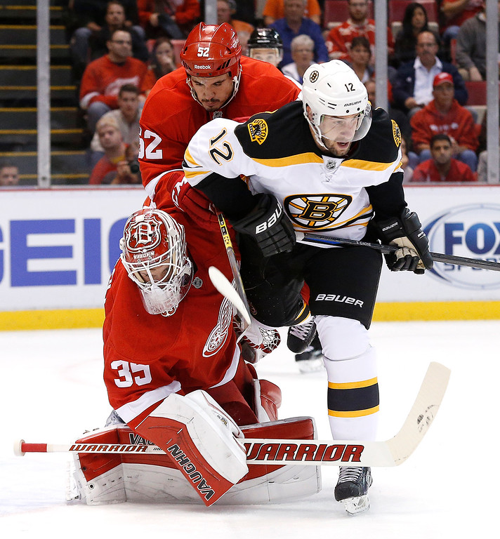 . Boston Bruins\' Simon Gagne (12) collides with Detroit Red Wings goalie Jimmy Howard (35) in the first period of an NHL hockey game in Detroit, Wednesday, Oct. 15, 2014. (AP Photo/Paul Sancya)