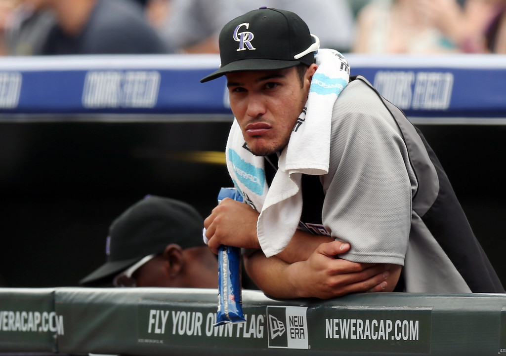 . Injured Colorado Rockies third baseman Nolan Arenado leans over the dugout rail to look on as the Rockies host the Los Angeles Dodgers in the first inning of a baseball game in Denver on Saturday, June 7, 2014. Arenado is on the 15-day disabled list with a fracture to his left middle finger. (AP Photo/David Zalubowski)