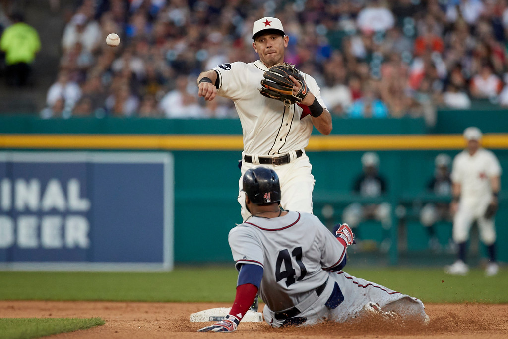 . Detroit Tigers second baseman Ian Kinsler, top, throws to first base to complete a double play as Cleveland Indians\' Carlos Santana (41) slides into second during the fifth inning in the second baseball game of a doubleheader in Detroit, Saturday, July 1, 2017. (AP Photo/Rick Osentoski)