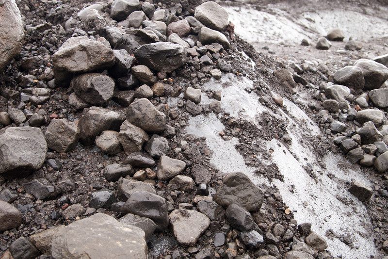 The base of the glacier is coated in rocks and gravel.  The slippery ice is directly underneath.