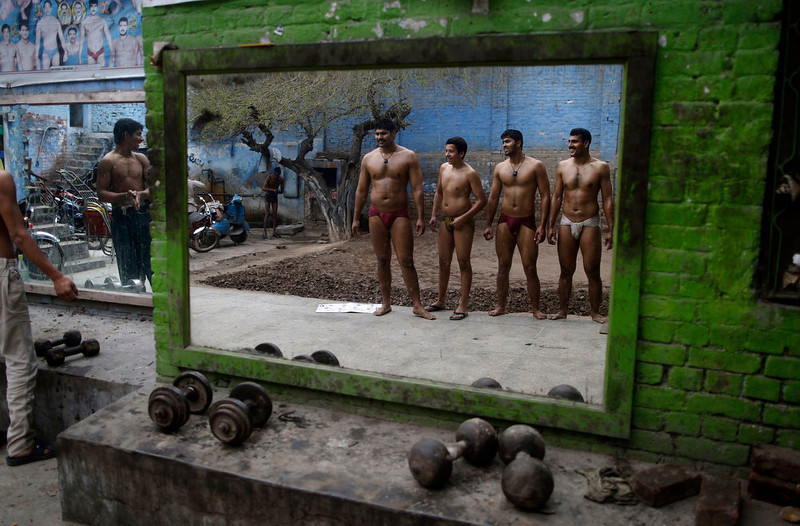 . Pakistani Kushti wrestlers, reflected on a mirror, following their daily training at a wrestling club in Lahore, Pakistan, Tuesday, Feb. 26, 2013. Kushti, an Indo-Pakistani form of wrestling, is several thousand years old and is a national sport in Pakistan. (AP Photo/Muhammed Muheisen)