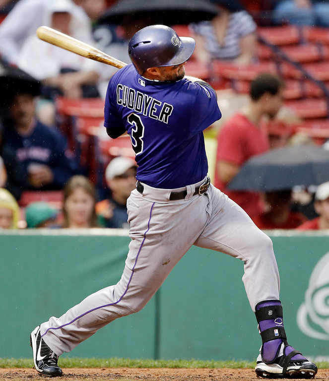 . Colorado Rockies\' Michael Cuddyer follows through on a solo home run against the Boston Red Sox during the eighth inning of an interleague baseball game at Fenway Park in Boston, Wednesday, June 26, 2013. It was his second homer of the game. The Red Sox won 5-3. (AP Photo/Elise Amendola)