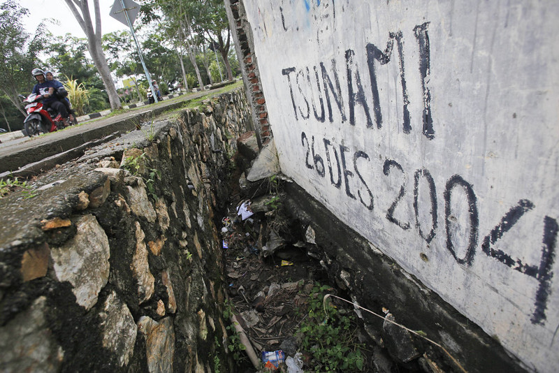 . Motorists ride past graffiti with the date of  the Indian Ocean tsunami, in Banda Aceh, Aceh province, Indonesia, Friday, Dec. 26, 2014. The devastating Boxing Day tsunami in 2004 struck a dozen countries around the Indian Ocean rim, killing 230,000 people, most of them in Aceh. (AP Photo/Binsar Bakkara)