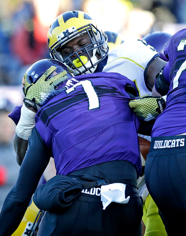 . Michigan defensive end Frank Clark (57) sacks Northwestern quarterback Matt Alviti (7) during the first half of an NCAA college football game in Evanston, Ill., Saturday, Nov. 8, 2014. (AP Photo/Nam Y. Huh)