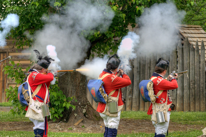 British reenactors fire on the settlers during the Siege of Fort Watauga at Sycamore Shoals State Park in Elizabethton, VA on Saturday, May 17, 2014. Copyright 2014 Jason Barnette  The Siege of Fort Watauga is a two-day reenactment held each year at the recreation of the fort inside Sycamore Shoals State Historic Park. The reenactment brings in dozens of reenactors and hundreds of visitors as they tell the story of an attack on the early settlers village by Dragging Canoe, and how they successfully defended themselves. During the reenactment, the fort is open to the public with demonstrations of all areas of early settler life on the frontiers.