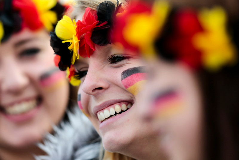 . Three women arrive at the airport Tegel to welcome German national soccer team in Berlin Tuesday, July 15, 2014. Germany beat Argentina 1-0 on Sunday to win its fourth World Cup title.  (AP Photo/Markus Schreiber)