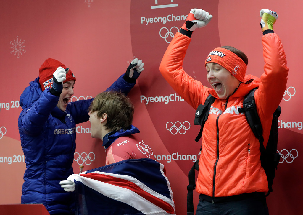. From left to right, Laura Deas of Britain, Lizzy Yarnold of Britain and Jacqueline Loelling of Germany shout as they realize Janine Flock of Austria dropped to fourth place in the finish area after the final run of the women\'s skeleton competition at the 2018 Winter Olympics in Pyeongchang, South Korea, Saturday, Feb. 17, 2018. Deas won bronze, Loelling won silver and Yarnold won the gold medal. (AP Photo/Wong Maye-E)