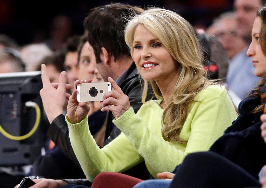 . Christie Brinkley takes a photo during the second half of an NBA basketball game between the New York Knicks and the Denver Nuggets on Friday, Feb. 7, 2014, in New York. The Knicks won the game 117-90. (AP Photo/Frank Franklin II)