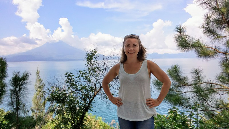 woman posing for photo in front of sea view with volcano in the background