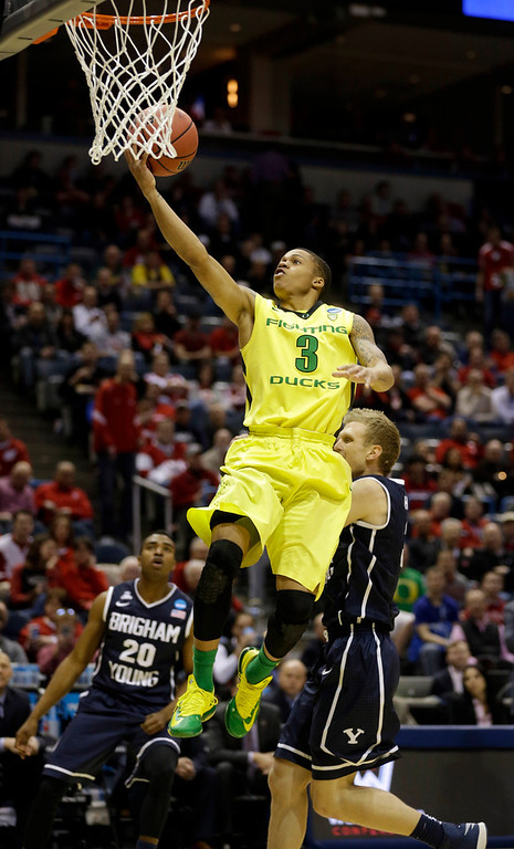 . Oregon guard Joseph Young (3) drives to the basket against BYU guard Tyler Haws (3) during the first half of a second-round game against the BYU in the NCAA college basketball tournament Thursday, March 20, 2014, in Milwaukee. (AP Photo/Jeffrey Phelps)