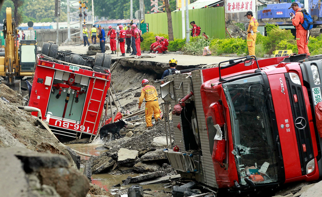 . Rescue workers use a sniffer dog to look for missing persons believed to be buried as firetrucks lie damaged after massive gas explosions in Kaohsiung, Taiwan, Friday, Aug. 1, 2014. A series of explosions about midnight Thursday and early Friday ripped through Taiwan\'s second-largest city, killing scores of people, Taiwan\'s National Fire Agency said Friday. (AP Photo/Wally Santana)