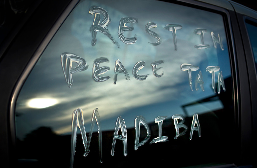 """. A message using Nelson Mandela\'s clan name \""""Madiba\"""" and a term of affection \""""Tata\"""" meaning \""""father\"""", is scrawled on the window of a car parked in the street outside Mandela\'s old house in Soweto, Johannesburg, South Africa Friday, Dec. 6, 2013. Flags were lowered to half-staff and people in black townships, in upscale mostly white suburbs and in South Africa\'s vast rural grasslands commemorated Nelson Mandela with song, tears and prayers on Friday while pledging to adhere to the values of unity and democracy that he embodied. (AP Photo/Ben Curtis)"""