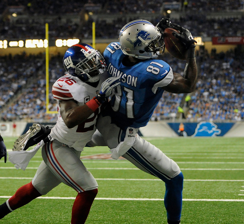 . Detroit Lions wide receiver Calvin Johnson can not haul in the pass as he is defended by New York Giants safety Antrel Rolle during the third quarter, Monday, Sept. 8, 2014, in Detroit, Mich.  The Lions defeated the Giants 35-14.  (The Oakland Press/Jose Juarez)