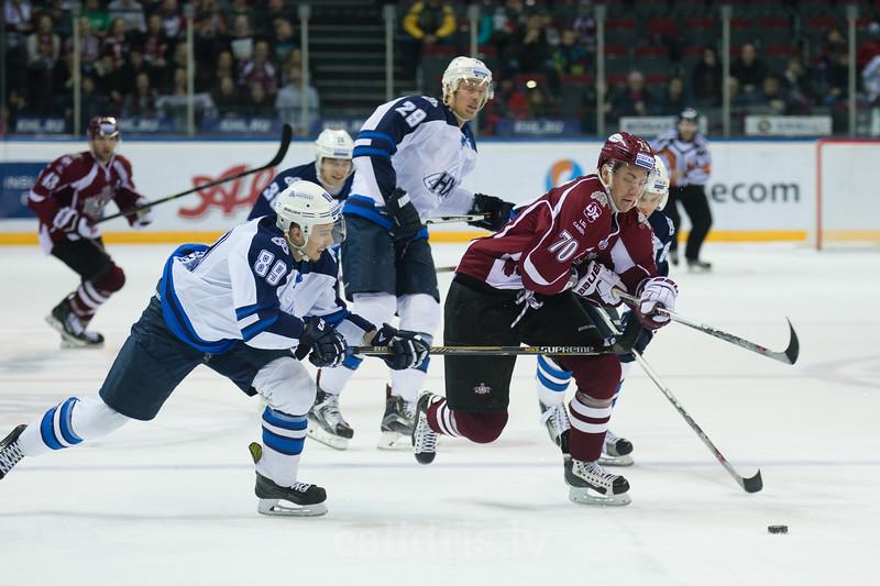 Denis Kuzmin (89) and Pavel Zdunov (95) try to stop Miks Indrasis (70) of Dinamo Riga
