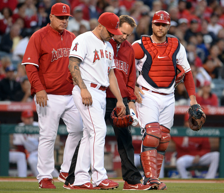 . Los Angeles Angels starting pitcher Hector Santiago, second from left, is looked at by a trainer after committing a throwing error on a ground ball by New York Yankees\' Brett Gardner (not pictured) in the first inning of a baseball game at Anaheim Stadium in Anaheim, Calif., on Wednesday, May 7, 2014.  (Keith Birmingham Pasadena Star-News)