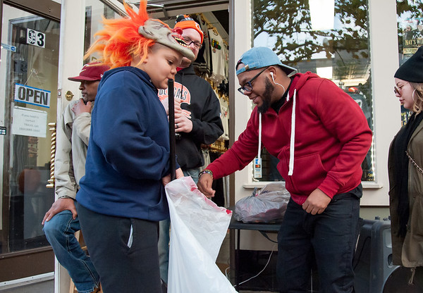 10/31/18 Wesley Bunnell | Staff Miciah Clark co-owner of So So Fly Clothing Store on West Main St stands outside of his store as he passes out candy to JEthan Pellot, age 11, during New Britain's Halloween Safe Zone event on Halloween.