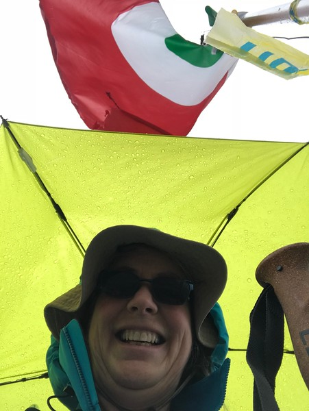 Selfie with the flag at the top above Rifugio Longoni