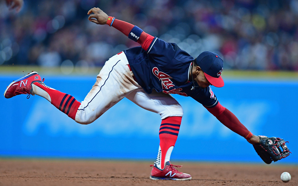 . Cleveland Indians\' Francisco Lindor reaches for the ball hit by Toronto Blue Jays\' Russell Martin, after being unable to barehand it, during the sixth inning of a baseball game Friday, April 13, 2018, in Cleveland. Lindor was charged with an error. (AP Photo/David Dermer)