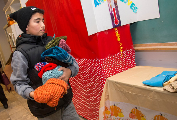 11/25/19 Wesley Bunnell | StaffrrThanksgiving meals were handed out by HRA Bristol on Monday evening by workers and volunteers. Volunteer Juan Martinez places more hand knitted hats and mittens onto a table for clients to take.