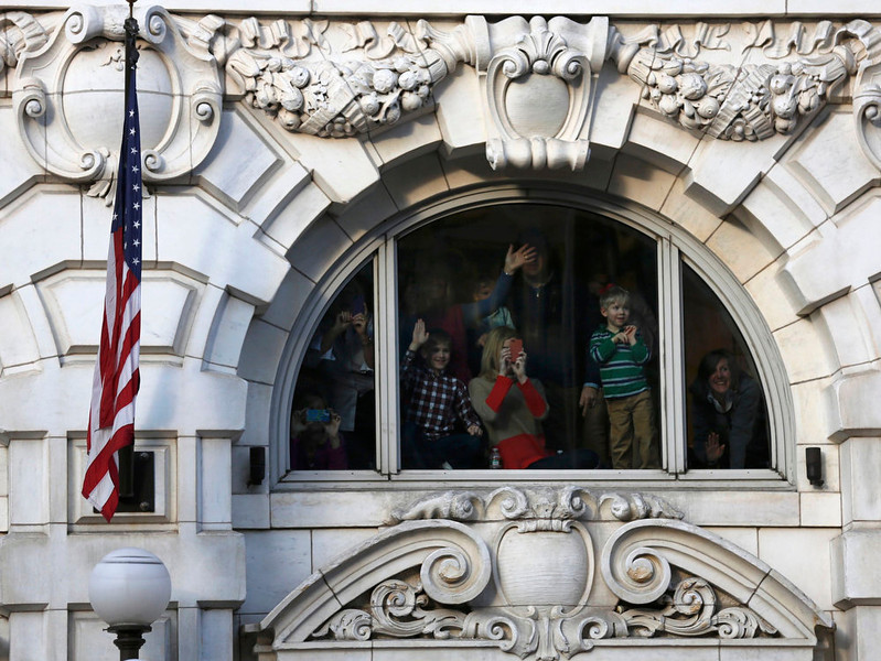. Spectators watch from behind a window as U.S. President Barack Obama and first lady Michelle Obama travel from the Capitol towards the White House during the inaugural parade in Washington, January 21, 2013.   REUTERS/Larry Downing