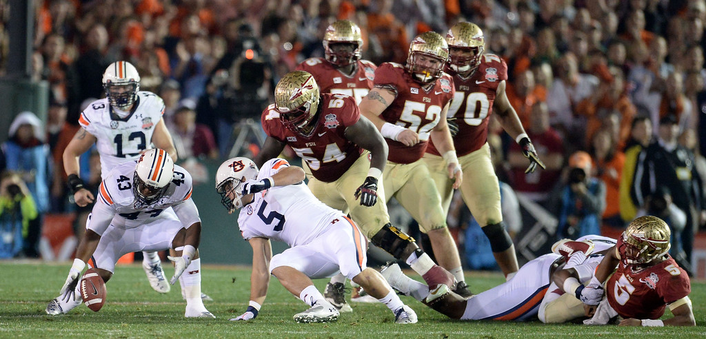 . Florida State quarterback Jameis Winston (5) fumbles as Auburn recovers in the first half of the BCS National Championship game at the Rose Bowl in Pasadena, Calif., on Monday, Jan. 6, 2014. 