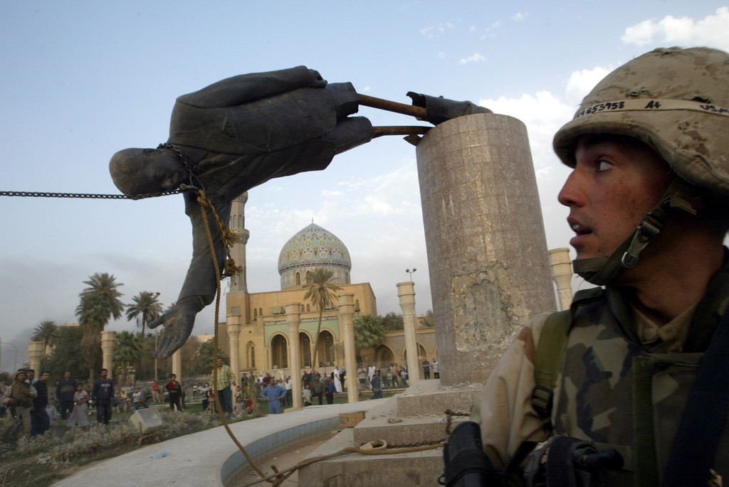 . U.S. Marine Corp Assaultman Kirk Dalrymple watches as a statue of Iraq\'s President Saddam Hussein falls in central Baghdad April 9, 2003. U.S. troops pulled down a 20-foot high statue of President Saddam Hussein REUTERS/Goran Tomasevic