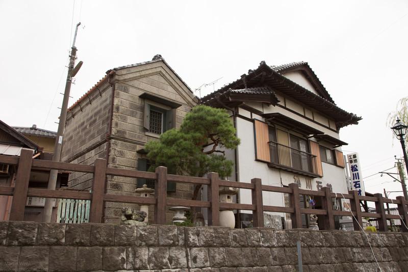 A beautiful stone storage house with a pine tree and stone lanterns. The house next shows cracks in the front from the earthquake in 2011.
