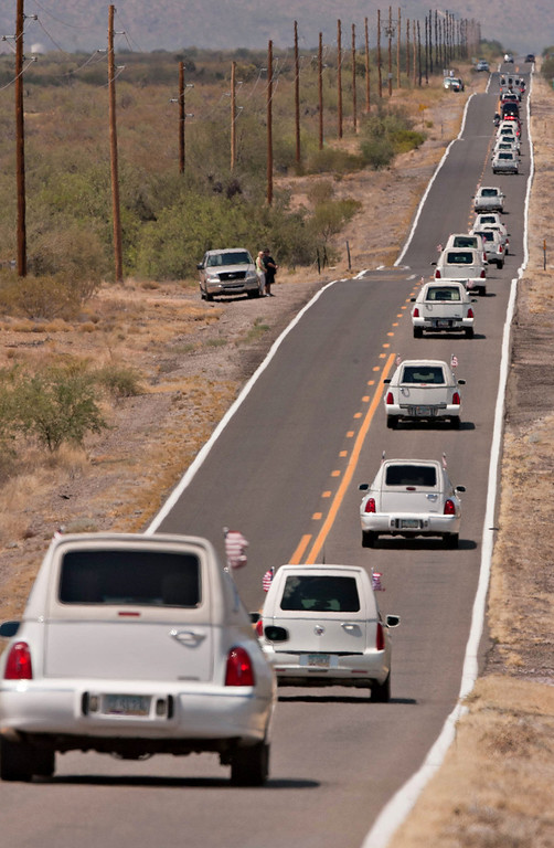 . A line of hearses makes their way north on Highway 89, south of Congress, Ariz. as the bodies of the 19 members of the Granite Mountain Hotshots were returned to Prescott, Ariz. from Phoenix, Sunday, July 7, 2013.  (AP Photo/The Arizona Republic, Tom Story)