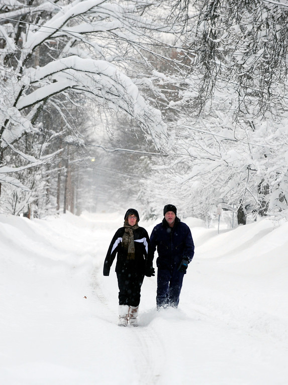 . Aileen Pawlowski and Gary Parker walk down Sycamore St. to get essentials from the local store in East Aurora, N.Y. Thursday Nov. 20, 2014. Foot traffic seems to be the best form of transportation after more snow fell last night and driving bans continue across Western New York. (AP Photo/Gary Wiepert)