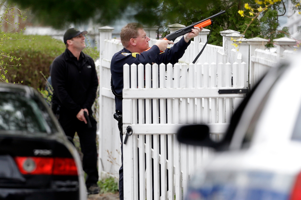 Description of . A police officer points his weapon at a residence as he conducts a search for a suspect in the Boston Marathon bombings, Friday, April 19, 2013, in Watertown, Mass. The two suspects in the Boston Marathon bombing killed an MIT police officer and hurled explosives at police in a car chase and gun battle overnight that left one of them dead and his brother on the loose, authorities said Friday as thousands of officers swarmed the streets in a manhunt that all but paralyzed the Boston area. (AP Photo/Matt Rourke)