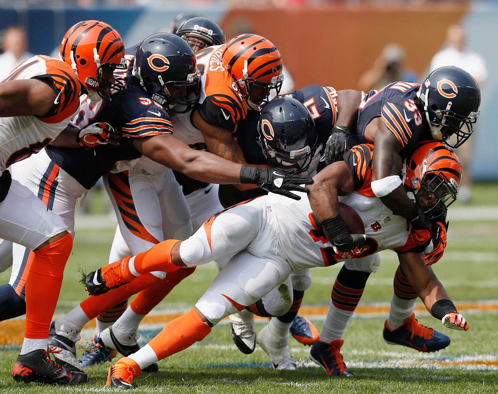 . Cincinnati Bengals running back BenJarvus Green-Ellis (42) is tackled by Chicago Bears cornerback Charles Tillman (33), safety Major Wright (21) and defensive end Corey Wootton (98) during the first half of an NFL football game, Sunday, Sept. 8, 2013, in Chicago. (AP Photo/Charles Rex Arbogast)