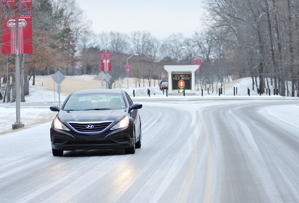 . A driver leaves the University of Mississippi campus in Oxford, Miss. on Tuesday, Feb. 11, 2014. Due to a thin layer of ice covered by snow that fell overnight, the university is closed until noon Tuesday. (AP Photo/Oxford Eagle, Bruce Newman)