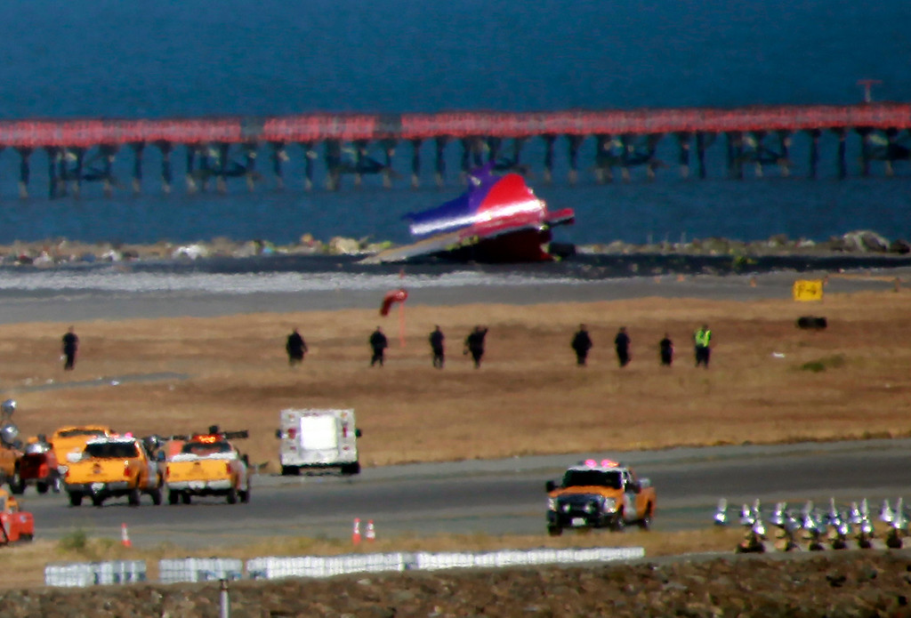 . Personnel combs through a debris field where an Asiana Airlines jet crashed when landing at San Francisco International Airport Saturday, July 6, 2013.  (Karl Mondon/Bay Area News Group)