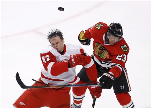 . Detroit Red Wings defenseman Alexei Marchenko (47) and Chicago Blackhawks right wing Kris Versteeg collide after going for a puck in the air during the overtime period of an NHL hockey game Wednesday, Feb. 18, 2015, in Chicago. The Red Wings won in a shootout 3-2. (AP Photo/Charles Rex Arbogast)