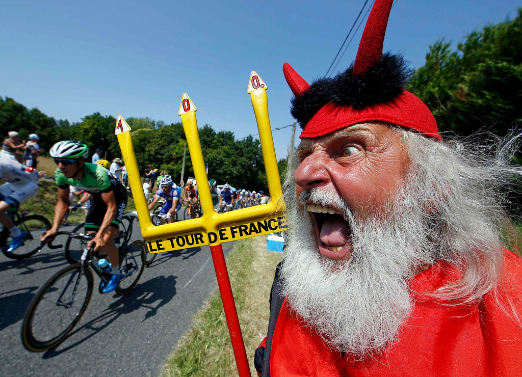 . The pack of riders makes its way past Didi Senft, a cycling enthusiast better known as \'El Diablo\' (The Devil), during the twelfth 218km stage of the centenary Tour de France cycling race from Fougeres to Tours July 11, 2013.    REUTERS/Eric Gaillard